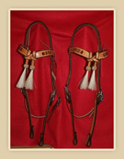 Matching set of headstalls crossed browband with horse hair tassles and rawhide braiding
