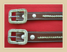 Matching pair of belts with rawhide accents and rawhide braided buckles.