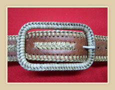 Custom made belt buckle with rawhide braid.
